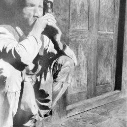 Sentado en la puerta fumando