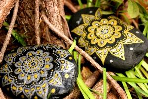 Piedra de la Costa Brava pintada con acrílico a pincel en tonos dorados y plateados sobre fondo negro