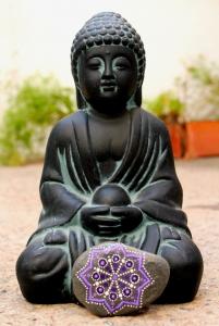 Piedra de la Costa Brava pintada con acrílico a pincel en tonos lilas.